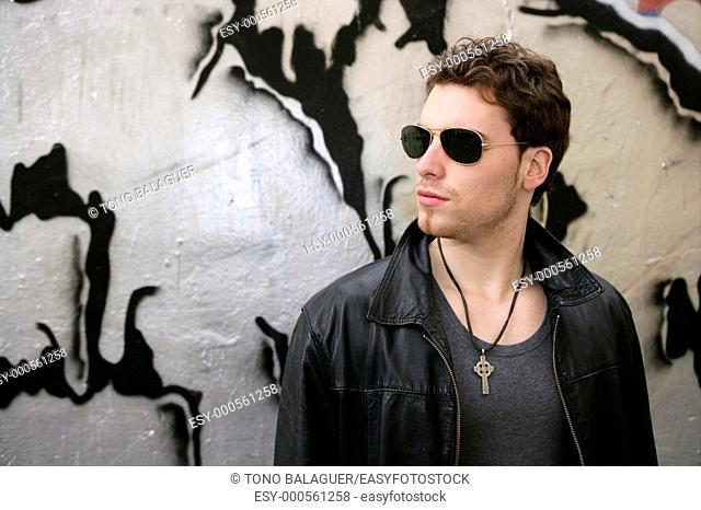 rocker rock star young man sunglasses on silver wall city outdoor
