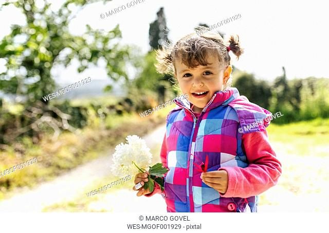 Portrait of smiling little girl with flower in her hand