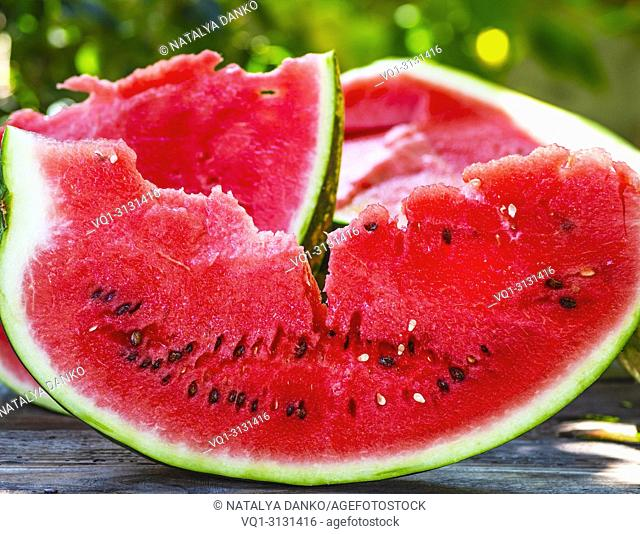 slice of ripe red watermelon with seeds on a wooden table, close up