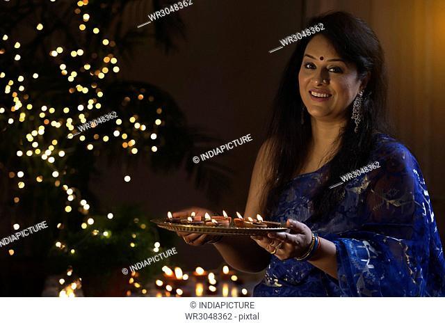 Woman with a tray of diya at a diwali festival