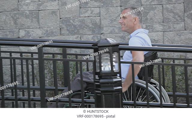 Man with spinal cord injury in a wheelchair using accessible wheelchair ramp uphill