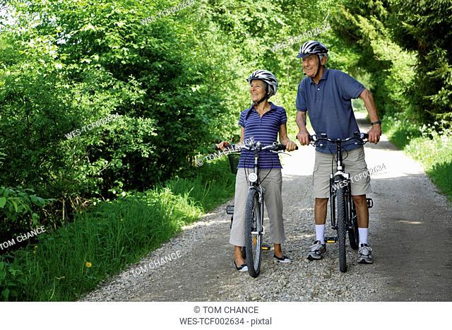 Germany, Bavaria, Senior couple with bicycle, smiling