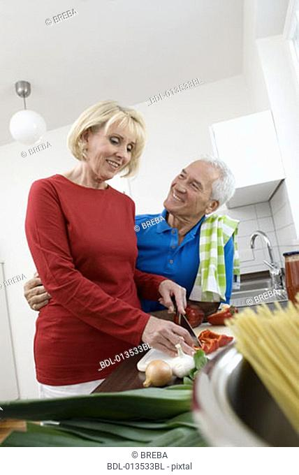 mature man embracing wife in kitchen while preparing meal