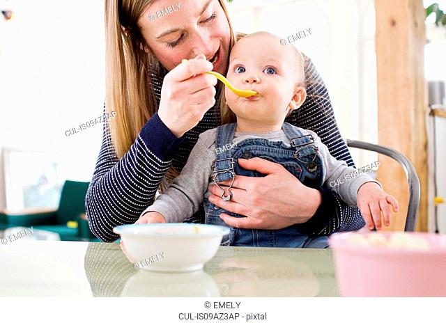 Mid adult woman feeding baby daughter at kitchen table