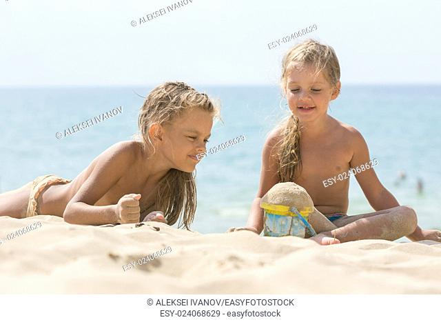 Two little girls are playing with enthusiasm in the sand on the seashore