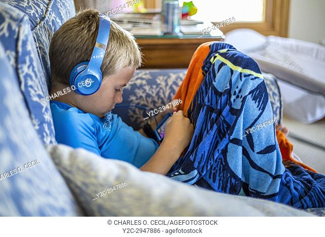 Avon, Outer Banks, North Carolina, USA. Young American Boy with his Mobile Gaming Device