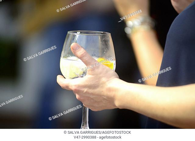 A woman's hand holding a glass with a cocktail of gin and tonic with ice and orange, at a quiet outdoor party