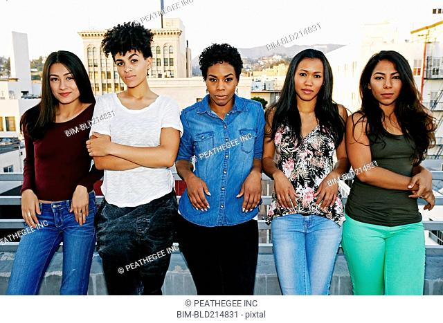 Serious women standing on urban rooftop