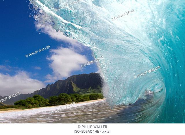Surface level view of curved ocean wave and beach, Hawaii, USA
