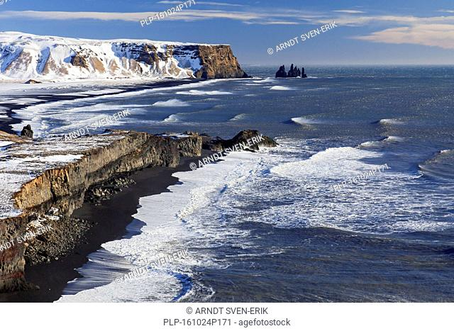 Reynisdrangar, basalt sea stacks in the snow in winter near the village Vík í Mýrdal, southern Iceland
