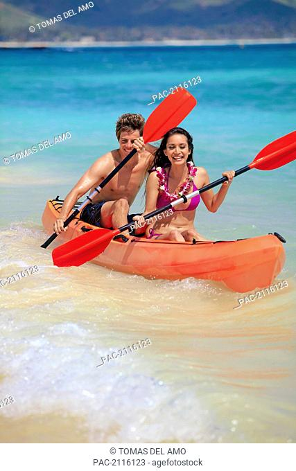 Hawaii, A Young Couple Paddling Their Kayak