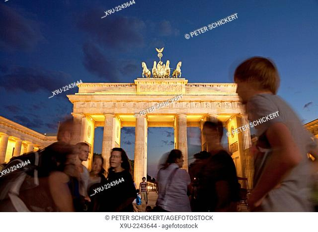 tourists at the illuminated Brandenburg Gate on Pariser Platz in Berlin, Germany, Europe