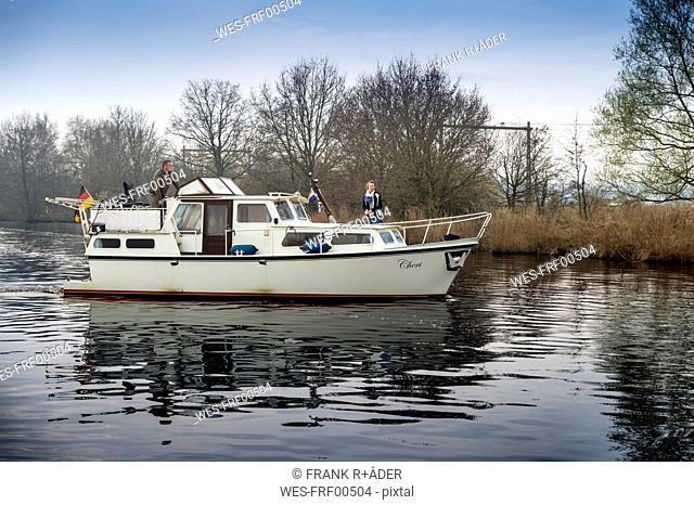 Netherlands, Friesland, Haskerdijken, couple on motorboat