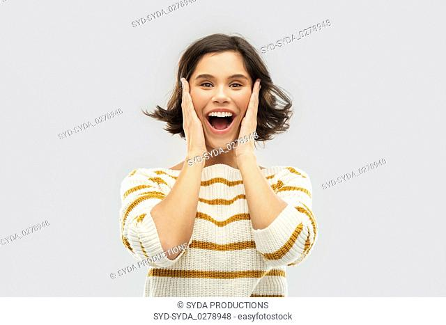 impressed woman in pullover holding to her face