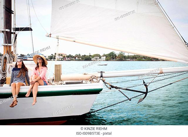 Two women on sitting on edge of sailing boat, legs dangling over the edge