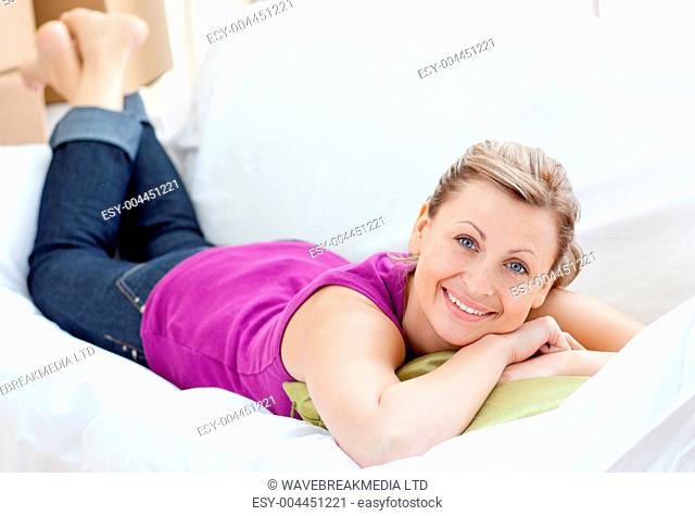 Portrait of a positive woman relaxing on a sofa with boxes