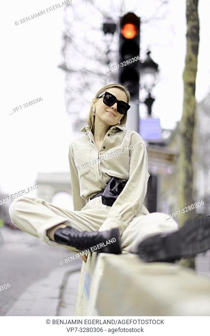 fashionable woman sitting on wall at street next to red traffic lights during fashion week, in Paris, France