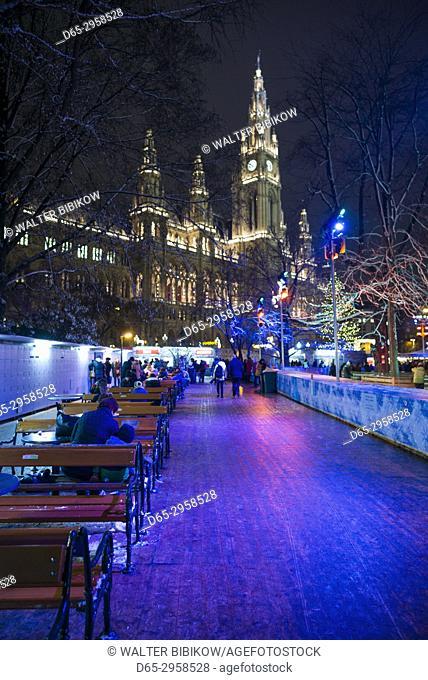 Austria, Vienna, Rathausplatz ice skating rink by Town Hall, Christmastime, evening