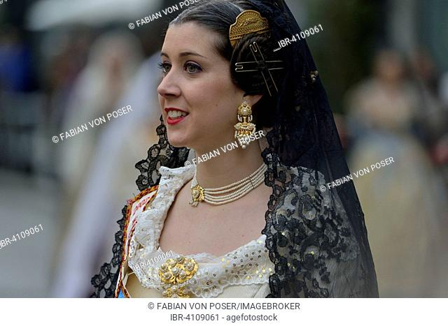 Fallas festival, woman in a traditional costume during the parade in the Plaza de la Virgen de los Desamparados, Valencia, Spain