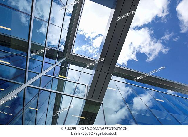 PUFFY WHITE CLOUDS BLUE SKY REFLECTED ON GLASS OFFICE BUILDING WINDOWS