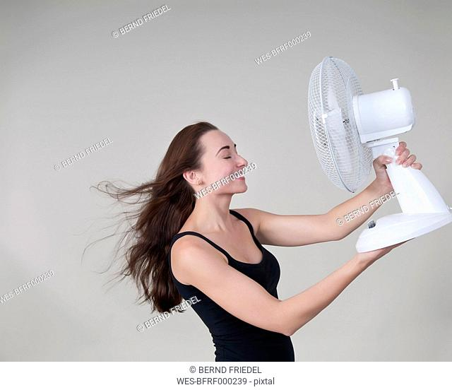 Young woman with electric fan, smiling