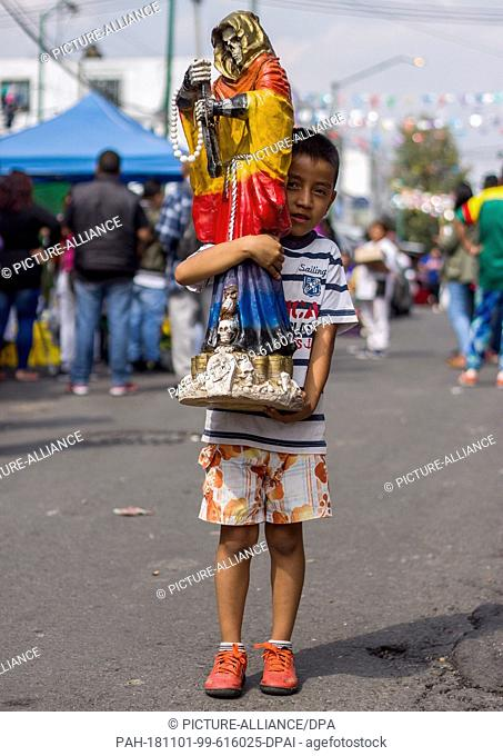 31 October 2018, Mexico, Mexico-City: A child carries a statue of the patron saint Santa Muerte to a shrine in the district of Tepito