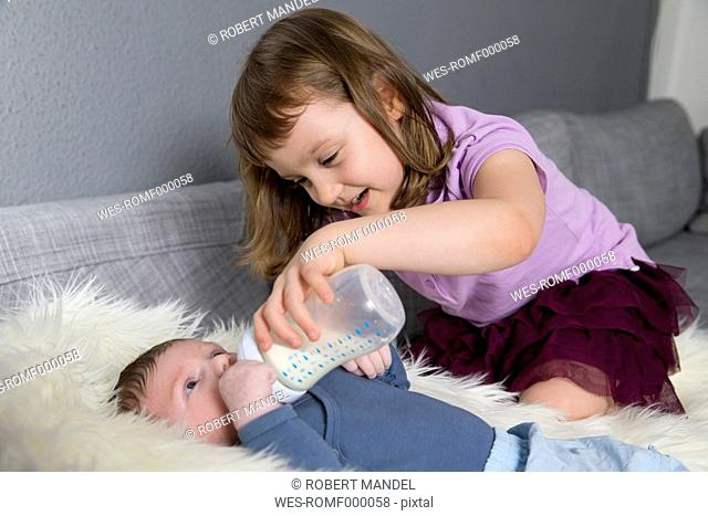 Little girl feeding newborn brother with baby bottle