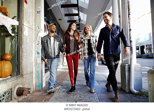 Two young men and two young women walking along a sidewalk, smiling