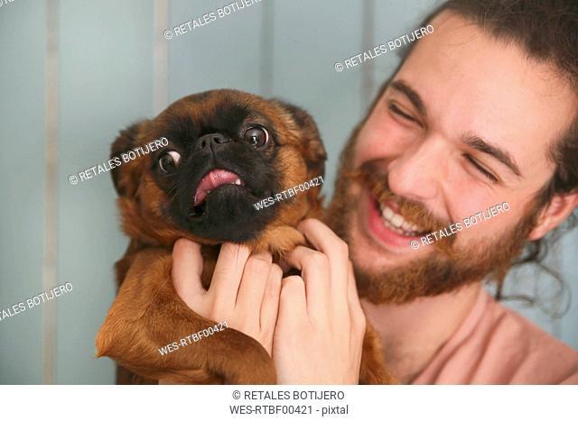 Laughing man holding Petit Brabancon