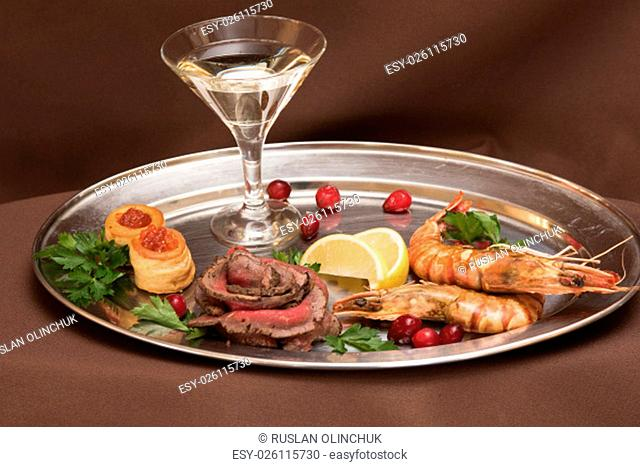 Grilled shrimps and beef meat on a plate