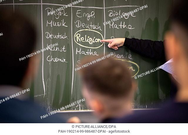 14 February 2019, North Rhine-Westphalia, Herford: ILLUSTRATION - Pupil Delin stands at a blackboard on which a timetable with religious instruction is written