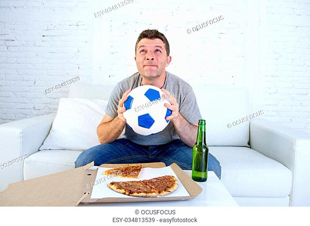young man alone in stress watching football game on television sitting at home living room sofa couch with ball , pizza box and beer bottle enjoying the match...