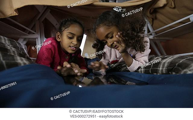 Cute little girls surfing the net on tablet