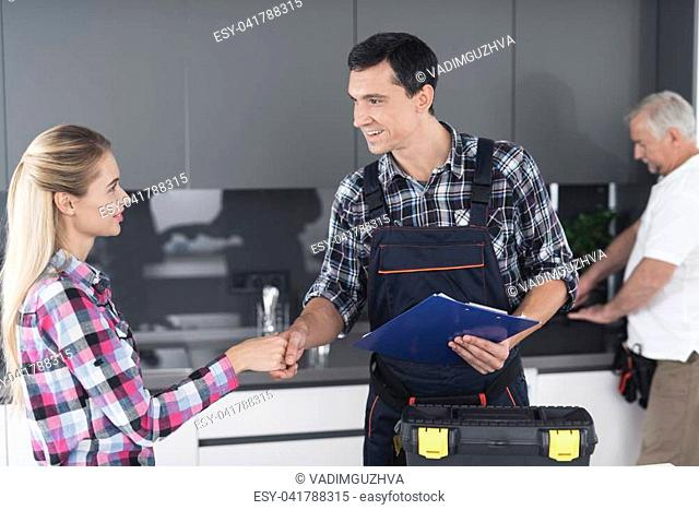 A woman signs a form for repair work by plumbers. She flirts with the young plumber. The second inspects the wash tap. A black box for tools is next to it