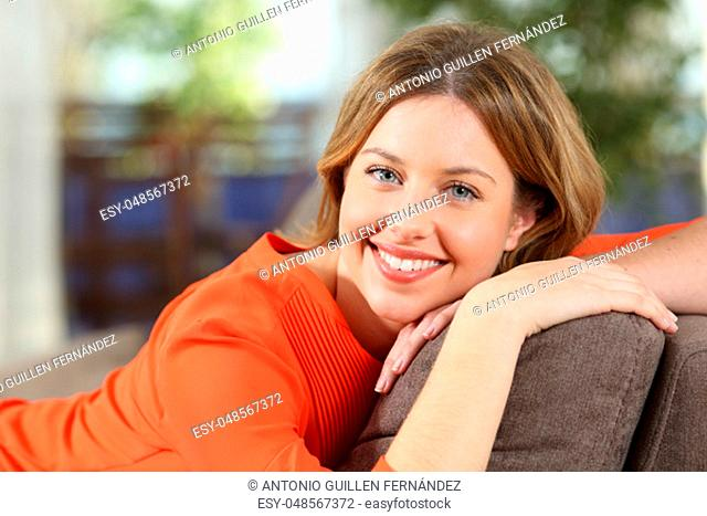 Happy woman posing sitting on a couch at home looking at camera