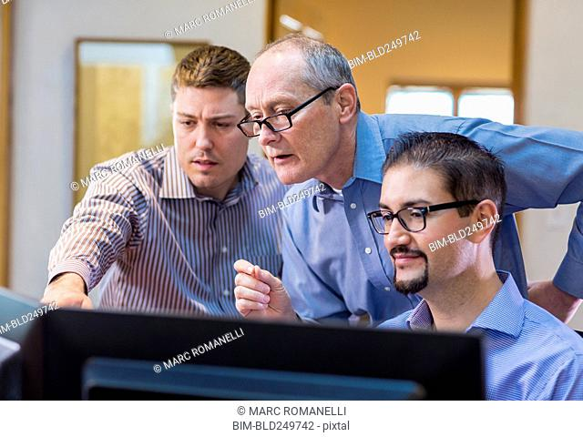 Businessmen talking in office near computer