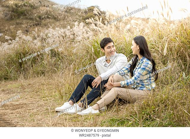 Smiling young couple sitting side by side face to face in silver grass field