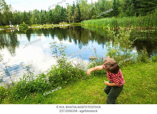 A young boy hurls a stone into a placid pond, Quebec, Canada