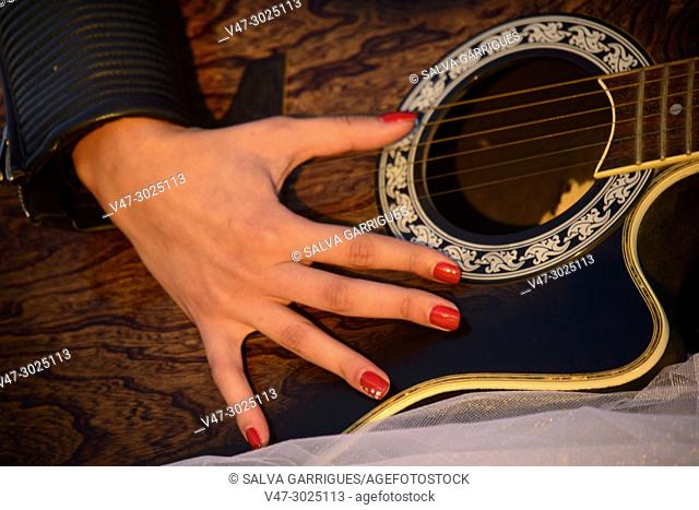 Hand with manicure and red nails of woman playing guitar guitar