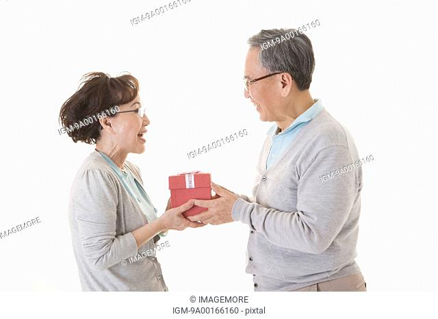 Senior couple holding gift and smiling together