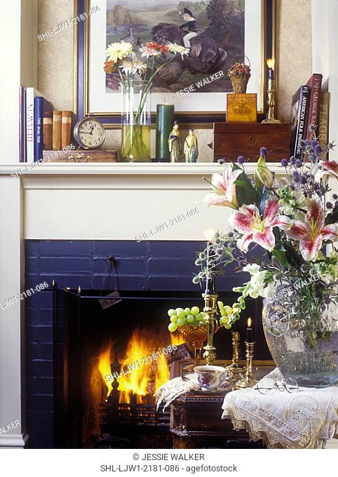 LIVING ROOMS - Detail of fireplace, foreground crystal vase with stargazer lilies, brass candlesticks, mantel display of books, asian sculptures, clock