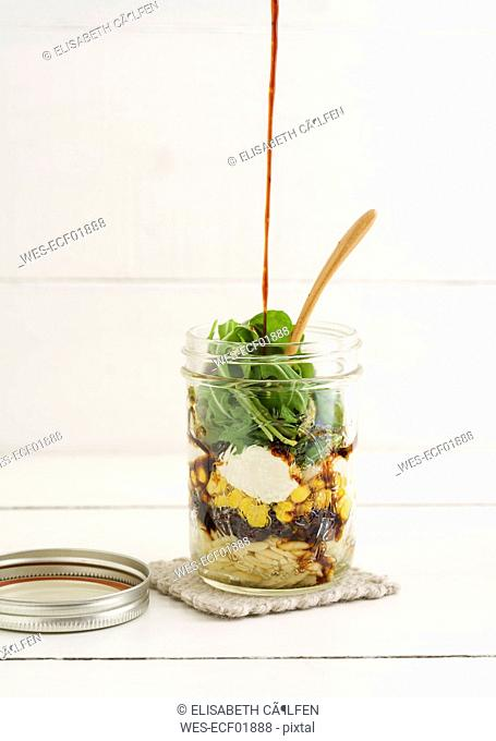 Jar of vegetarian mixed salad with Kritharaki, corn, rocket and cranberries and balsamico vinegar