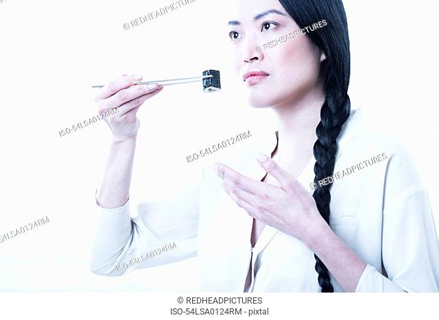 Woman smelling piece of sushi