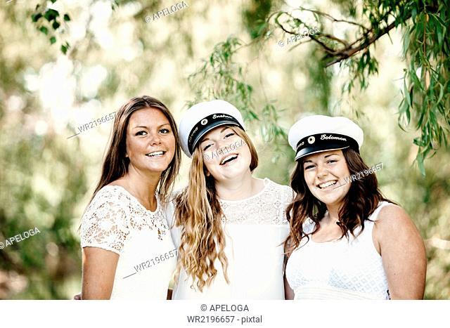 Portrait of happy female graduates at university park