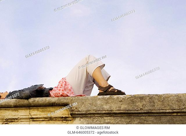 Low angle view of a young woman lying on a stone wall