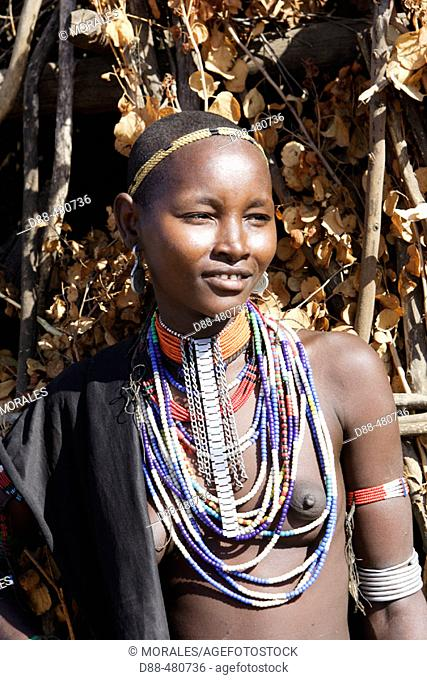 Young Erbore tribe girl in front of her straw and wooden hut. Shepherds tribe from south Ethiopia