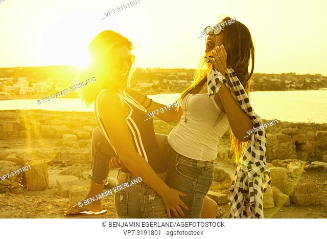 two women at ancient ruins, friends, seaside, fun, happy, together, holiday, in Chersonissos, Crete, Greece