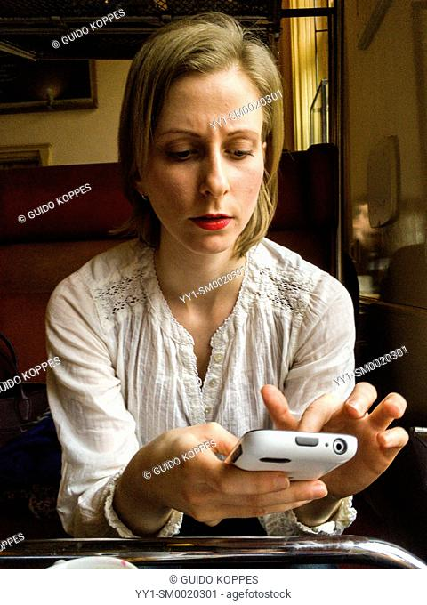 Tilburg, Netherlands. Caucasian female reading messages on her smartphone while visiting a cafe during a meeting
