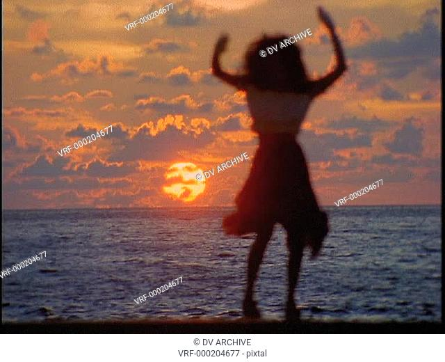 A woman shakes her stuff in front of the ocean during a beautiful golden-hour