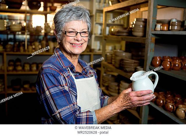 Portrait of female potter holding jug
